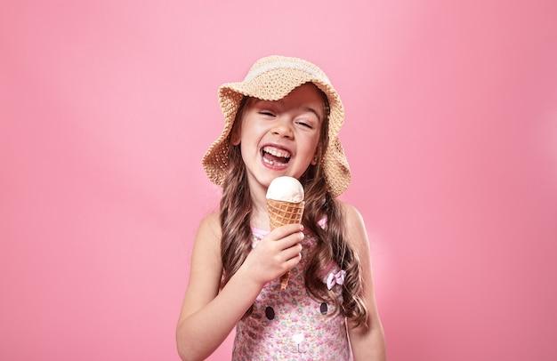 色付きの背景にアイスクリームと小さな陽気な女の子の肖像画