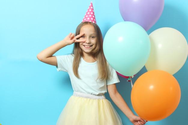 축제 모자와 풍선과 함께 작은 귀여운 소녀의 초상화