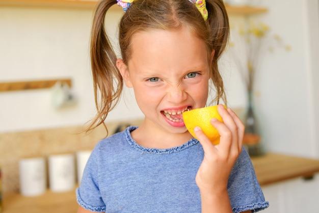 식료품과 건강에 좋은 음식을 들고 부엌에 있는 귀여운 소녀의 초상화