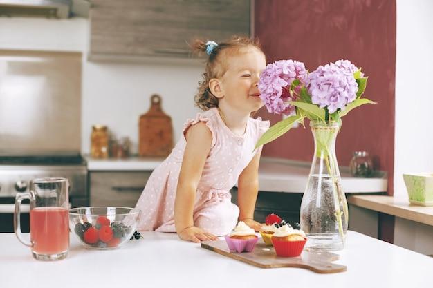 Портрет маленькой милой девочки нюхает гортензии