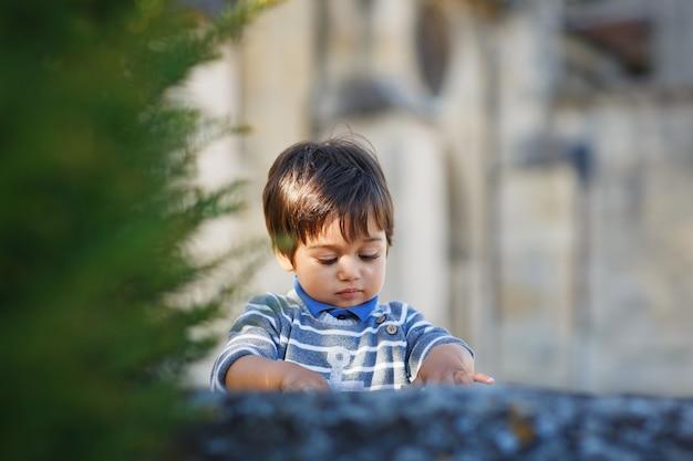 公園で屋外で遊んでいる小さな東部のハンサムな男の子の肖像画。水たまりに小さな岩がある通りでアラビアの子供が楽しい