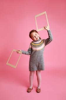 ピンクの背景にモックアップのための2つの空白のフレームを保持している小さな面白い女の子の肖像画