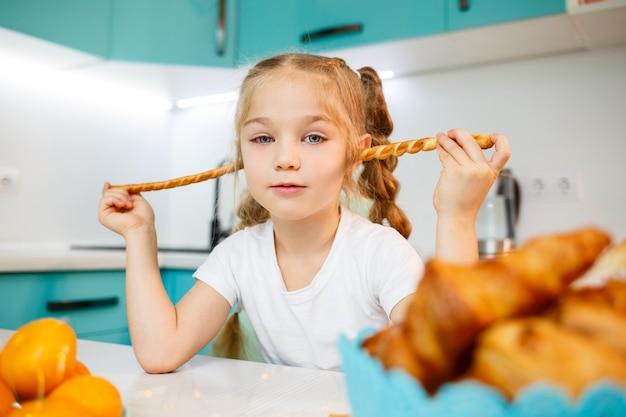 7세 소녀의 초상화는 부엌에 앉아서 빵 막대기를 가지고 노는다. 아이는 부엌에서 아침을 먹는다