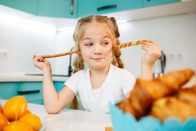 7歳の少女の肖像画は、キッチンに座って、パン棒で遊んでいます。子供は台所で朝食をとります