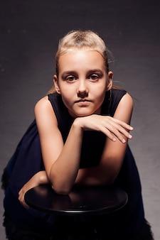 스튜디오의 어두운 배경에서 격리된 어두운 푹신한 치마를 입은 8-10세 소녀의 초상화.