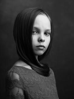 흑백 사진을 포즈를 취하는 어린 소녀 클로즈업의 초상화. 고품질 사진