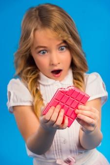 ピンクのチョコレートを食べる少女の肖像画。