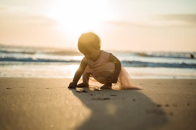 해변에서 휴가를 즐기는 어린 소녀의 초상화는 모래 놀이를 즐길 수