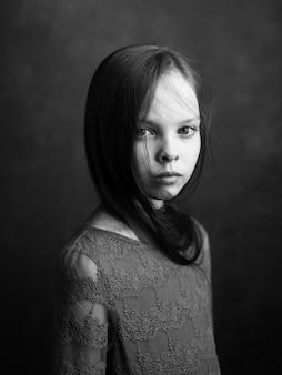 어두운 회색 배경 사진에 드레스에 어린 소녀의 초상화 자른 측면보기