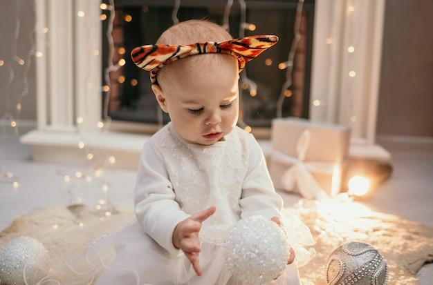 ふわふわの白いドレスとクリスマスツリーのおもちゃと暖炉の近くの部屋に座っている虎の耳を持つヘッドバンドの少女の肖像画