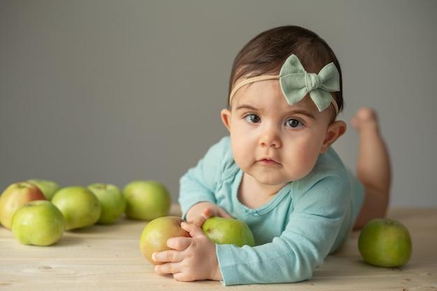 신선한 녹색 사과와 나무 테이블에 녹색 bodysuit에서 어린 소녀의 초상화. 어린이를 위한 천연 제품. 고품질 사진