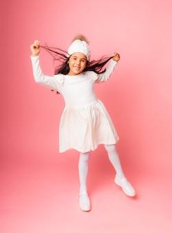 ピンクの背景に白い冬の帽子と白いドレスを編んだ少女の肖像画