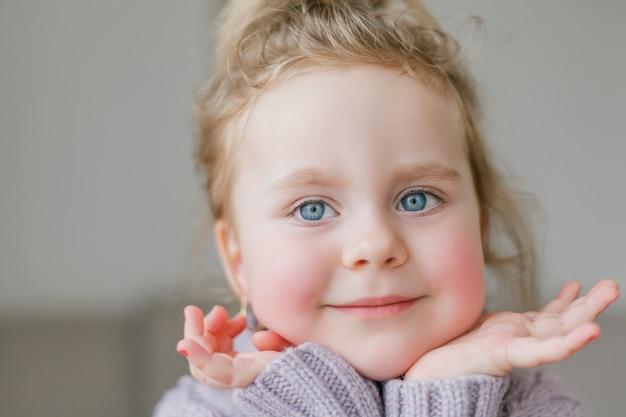 라일락 니트 스웨터에 어린 소녀의 초상화. 행복한 아이. 기분 좋은.