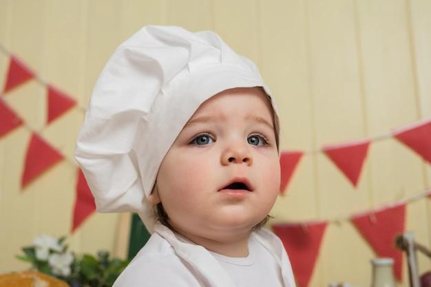 흰색 요리사의 모자에있는 어린 소녀의 초상화