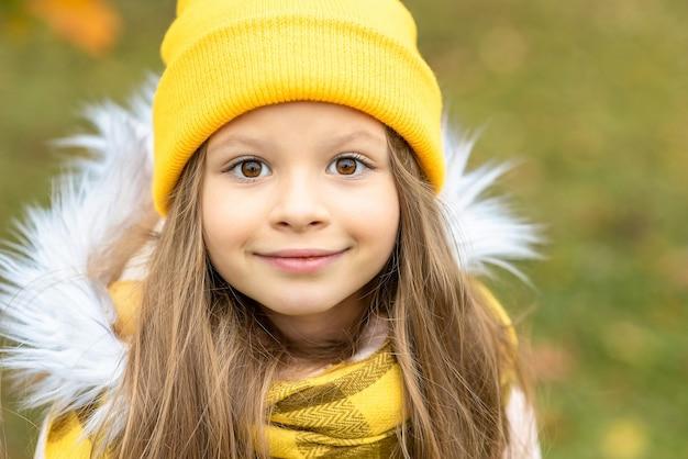 黄色い帽子をかぶった少女の肖像画。