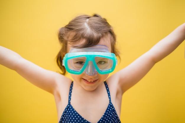 Портрет маленькой девочки в плавательных очках на желтом фоне изолированные с пространством для текста