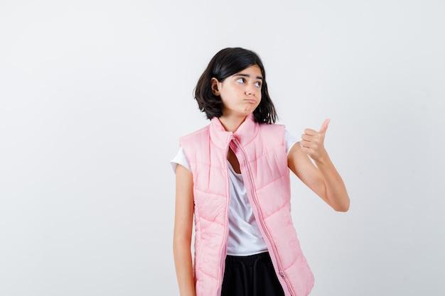 Портрет маленькой девочки в белой футболке и пуховике, показывая большой палец вверх