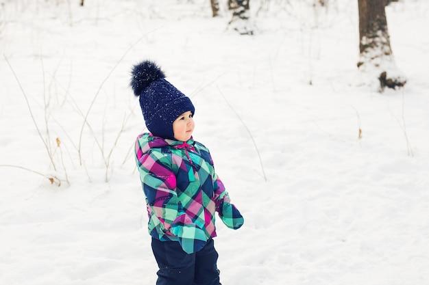 눈송이 배경에서 눈 숲에서 겨울 옷에 어린 소녀의 초상화.