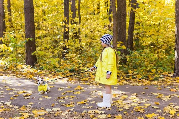 주황색과 노란색의 배경에 어린 소녀의 초상화는 단풍 화창한 날에 나뭇잎
