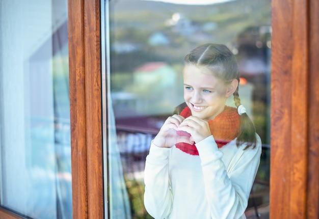 Портрет маленькой девочки за окном, которая общается руками на языке жестов.
