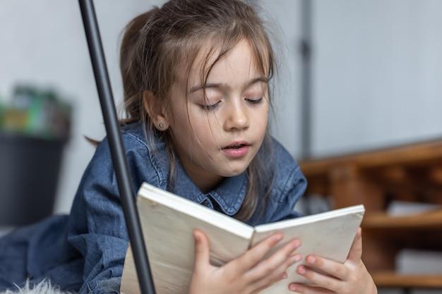 Портрет маленькой девочки, читающей книгу, лежащую на полу в комнате.