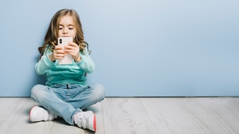 Portrait of a little girl sitting on hardwood floor looking at smartphone