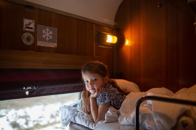Портрет маленькой девочки, путешествующей в российском поезде, интерьер поезда, купе.