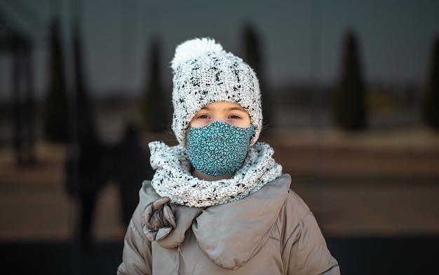 コロナウイルスのパンデミック時に帽子とマスクをかぶった少女の肖像画。