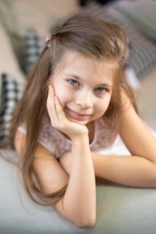 彼女の腕に寄りかかって、ソファに横たわっている少女の肖像画。