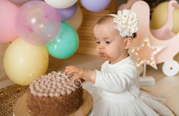 Портрет маленькой девочки с грязным лицом, едящей торт руками