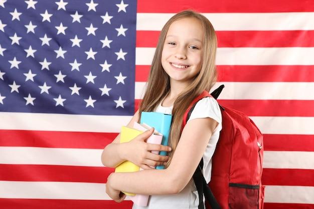학교 배낭과 미국 국기를 든 어린 소녀의 초상화