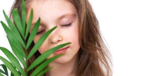 Портрет маленькой девочки с закрытыми глазами и милой улыбкой, покрытой зеленым листом пальмы. сосредоточьтесь на глазах
