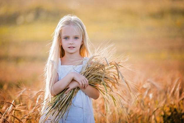 필드에 서있는 그녀의 손에 어깨 나무와 흰 드레스에 긴 금발 머리를 가진 어린 소녀의 초상화