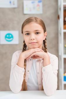 Портрет маленькой девочки с длинной косой, смотрящей на камеру