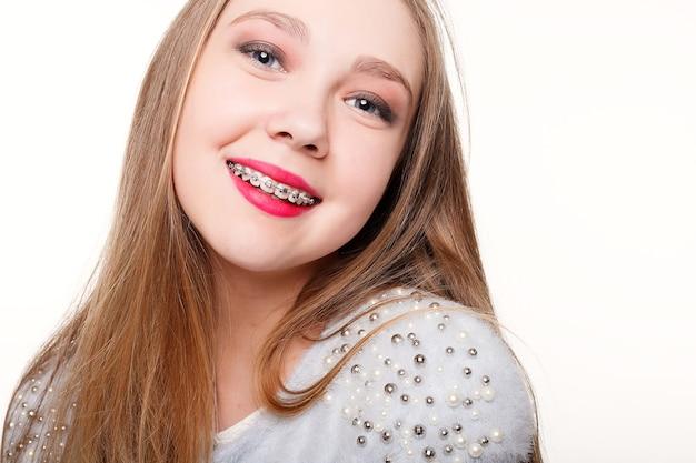 歯科矯正器具を持った少女の肖像画。