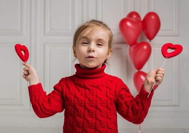 Портрет маленькой девочки с красными сердечками на палочке на белом
