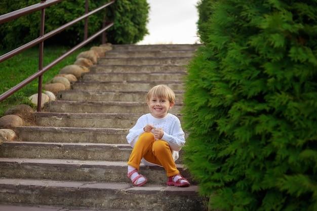 .портрет маленькой девочки с короткими волосами, сидящей на лестнице в парке.