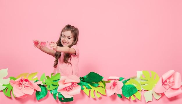 Портрет маленькой девочки с очками на розовой стене