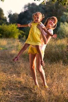 Портрет маленькой девочки со старшей сестрой-подростком на природе на фоне травы и деревьев