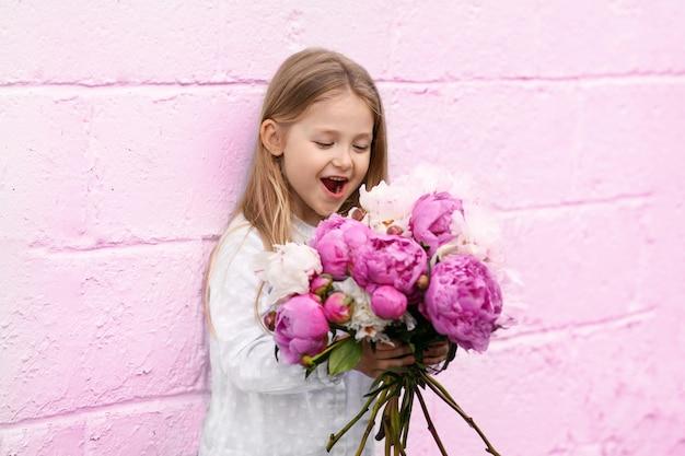 ピンクの壁の近くに牡丹を持つ少女の肖像画