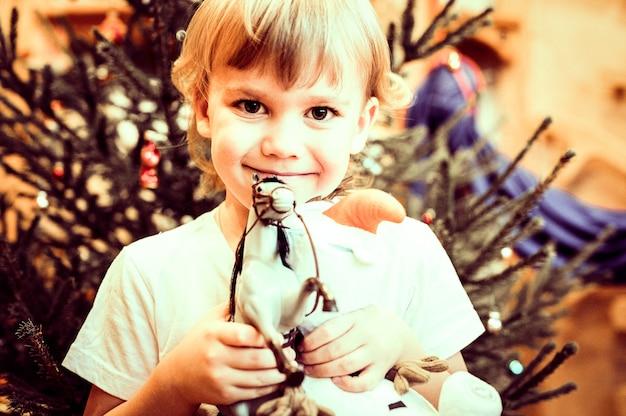 손에 장난감 말 선물을 들고 있는 행복한 5세 소년의 초상화는 집에서 새해를 축하하는 동안 크리스마스 트리 배경에 있는 카메라를 쳐다봅니다.