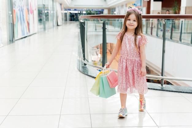 Портрет маленькая счастливая девушка в торговом центре. улыбающаяся смеющаяся девушка в розовом платье с разноцветными сумками в руках прогуливается по торговому центру, глядя на витрины магазина