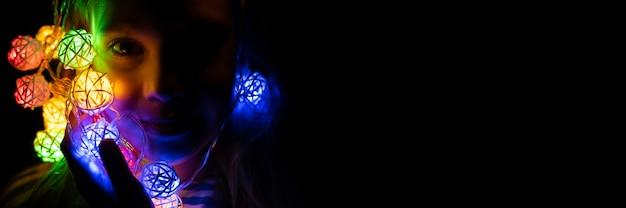 집에서 밤 시간에 여러 가지 빛깔의 네온 불빛으로 빛나는 그녀의 얼굴 근처에 손에 화환을 들고 있는 어린 소녀의 초상화. 크리스마스 이브 휴일 축 하입니다. 배너. 텍스트를 위한 공간