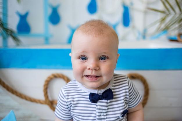 青と白の木製ボートの横に座って、カメラを見ている縞模様のジャンプスーツの小さな子供の肖像画