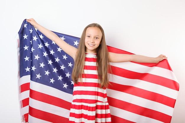그녀의 손에 미국 국기와 함께 긍정적인 소녀의 초상화