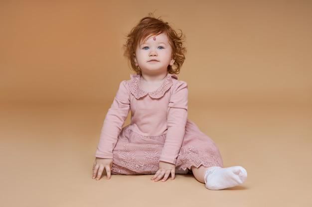 巻き毛の小さな赤い髪の少女の肖像画。子供の額に大きなほくろ Premium写真