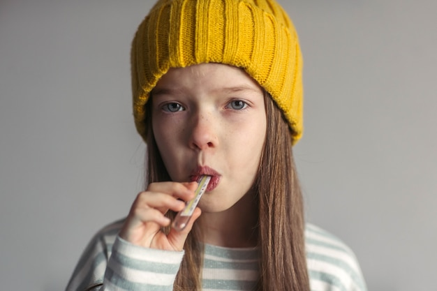 インフルエンザウイルスの鼻水と頭痛に苦しんでいる帽子をかぶった小さな悲しい不幸な少女の肖像画は、温度計で温度を測定します
