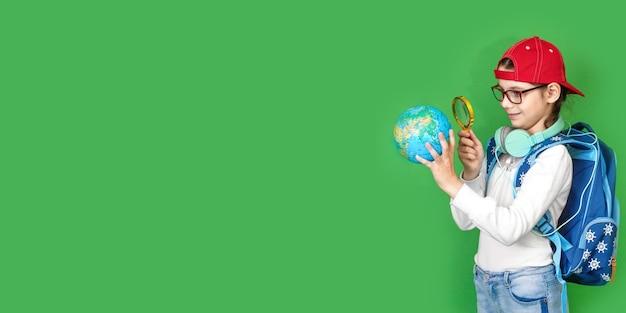 Портрет маленькой школьницы с рюкзаком, держа в руках глобус, улыбаясь на желтом фоне. обратно в школу. новый учебный год. концепция детского образования. широкий баннер. копировать пространство