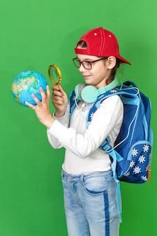 黄色の背景に笑みを浮かべて彼女の手で地球儀を保持しているバックパックを持つ小さな女子高生の肖像画。学校に戻る。新しい学年。子供の教育の概念。