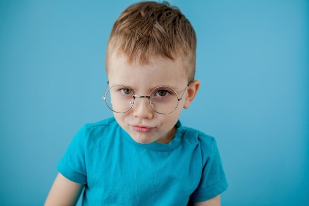 面白いメガネの小さな笑みを浮かべて男の子の肖像画。学校。未就学。ファッション
